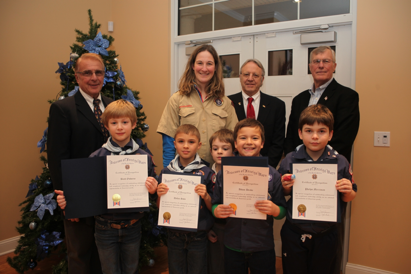 At the December holiday dinner of Metacomet VFW Post 1926 in Simsbury, five certificates of recognition were distributed to members of the Simsbury Cub Scout Den 11 of Boy Scout Pack 276 for their outstanding contribution of $486 to the Post's 'Adopt a Vet' program.  The Cub Scouts raised the donation by selling Boy Scout popcorn. The Post's 'Adopt A Vet' program has been in place for just over one year with the long term objective to help individual veterans stand on their own in a sustaining lifestyle.  The program recently helped a disabled veteran financially while appealing his disability with the Veterans Administration and helped a homeless veteran get back on his feet.  The Cub Scouts responsible for the donation, with their certificates, are (left to right): Brett Osborne, Dylan Soto, Aiden Drake, Phelps Merriman. Missing from the picture is Caleb Deems.  In the back row are (left to right): John Romano, Commander, VFW Post 1926; Suzanne Osborne, Den Leader with her son, Josh; John Lamb, Quartermaster of Post 1926; and John Fox, Senior Vice Commander of Post 1926.